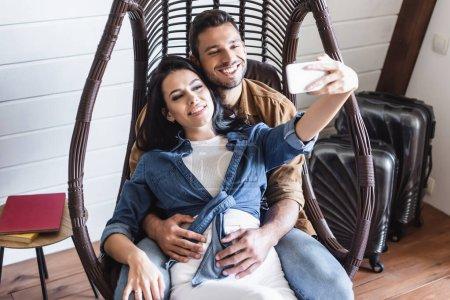 Photo pour Couple joyeux prenant selfie sur smartphone tout en étant assis dans une chaise en rotin suspendu - image libre de droit