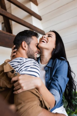 Photo for Brunette woman laughing with closed eyes while hugging boyfriend on wooden stairs at home, blurred foreground - Royalty Free Image