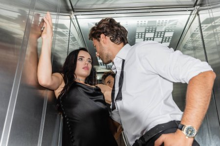 low angle view of man seducing sexy woman in black satin dress in elevator