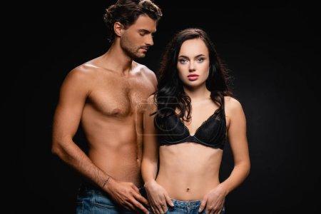 Photo pour Femme sexy avec les mains dans les poches regardant la caméra près sexy homme torse nu isolé sur noir - image libre de droit