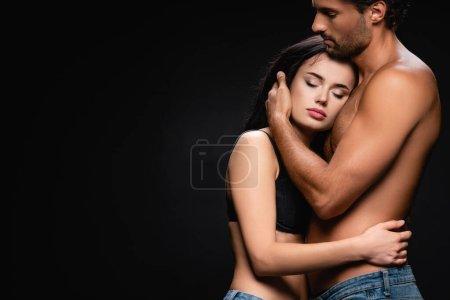 Photo pour Jeune homme torse nu embrassant femme brune sensuelle isolé sur noir - image libre de droit