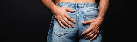 vue recadrée de la femme en jeans près de l'homme embrassant ses fesses isolées sur noir, bannière