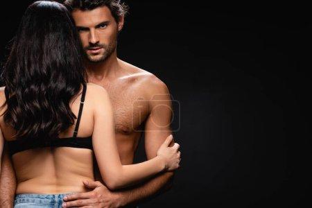 Photo pour Jeune homme torse nu regardant la caméra tout en embrassant femme brune sexy isolé sur noir - image libre de droit