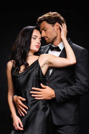 Photo pour Femme sensuelle en robe élégante touchant la tête du jeune homme embrassant son isolé sur noir - image libre de droit