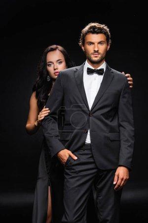 junger selbstbewusster Mann mit der Hand in der Tasche in der Nähe einer sinnlichen brünetten Frau auf Schwarz