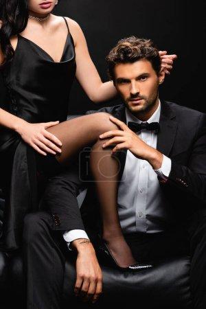 Foto de Hombre joven en traje tocando la pierna de la mujer sensual mientras mira la cámara aislada en negro - Imagen libre de derechos