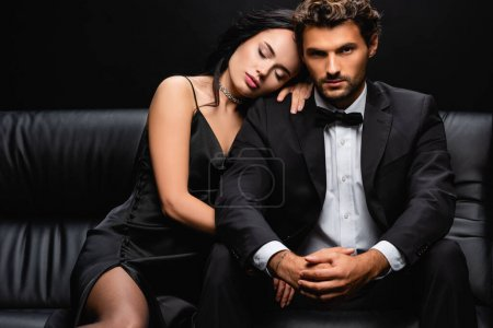 sexy woman in satin dress lying on shoulder of elegant man sitting on leather couch isolated on black