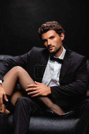 Photo pour Jeune homme élégant regardant la caméra tout en touchant les jambes de la femme séduisante isolé sur noir - image libre de droit