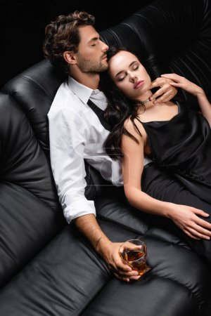 high angle view of man with glass of whiskey and sexy woman in satin dress on leather sofa isolated on black