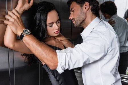 young elegant man hugging neck of seductive brunette woman in elevator