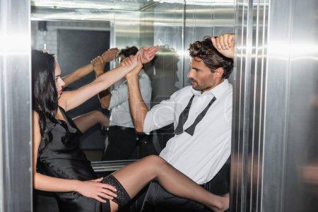 Photo pour Jeune homme tenant la main d'une femme passionnée tout en la séduisant dans l'ascenseur - image libre de droit