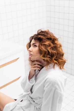 Pensive woman in white bathrobe looking away in bathroom