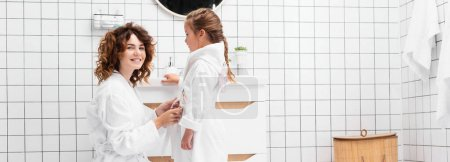 Photo for Smiling woman wearing bathrobe on daughter in bathroom, banner - Royalty Free Image