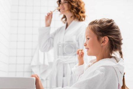 Cheerful girl in bathrobe brushing teeth near sink and mother on blurred background