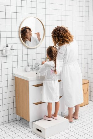 Photo for Woman and child brushing teeth near mirror and sink in bathroom - Royalty Free Image