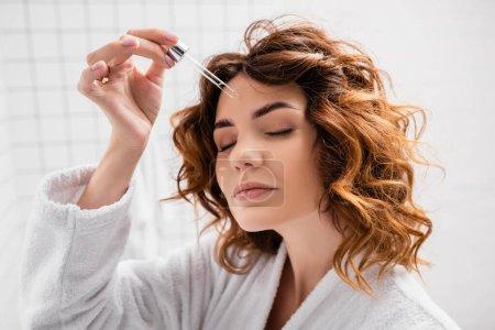 Curly woman applying cosmetic serum in bathroom