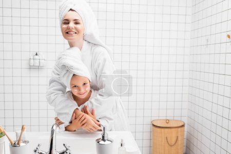 Photo for Smiling woman in towel and bathrobe hugging daughter with cream on face - Royalty Free Image