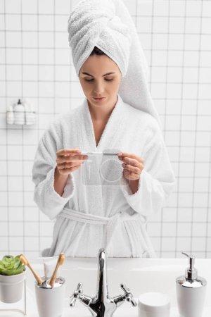 Photo pour Femme tenant test de grossesse près de l'évier dans la salle de bain - image libre de droit