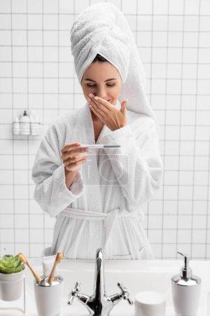 Photo pour Femme incroyable en serviette et peignoir tenant test de grossesse dans la salle de bain - image libre de droit