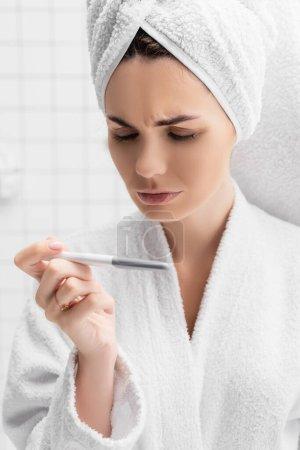 Photo pour Femme concentrée avec serviette sur la tête regardant le test de grossesse - image libre de droit