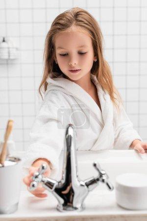 Photo pour Fille ouvrant l'eau près de l'évier sur le premier plan flou dans la salle de bain - image libre de droit