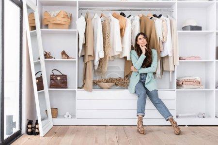 Pensive woman sitting on shelf in wardrobe