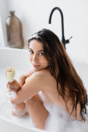 Brunette woman looking at camera while holding glass of champagne in bathtub