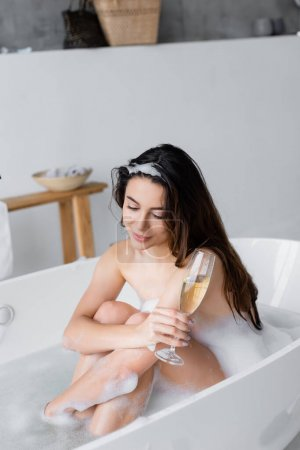Smiling brunette woman relaxing in bathtub with glass of champagne