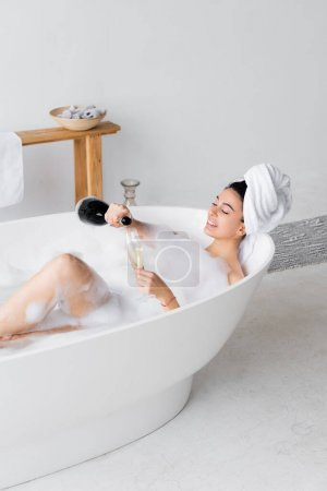 Smiling woman pouring champagne in glass in bathtub