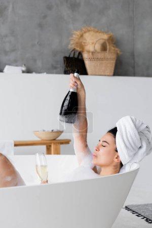 Femme en mousse tenant bouteille et verre avec champagne dans la baignoire