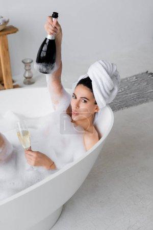 Junge Frau mit Champagner blickt in Badewanne mit Schaum in die Kamera