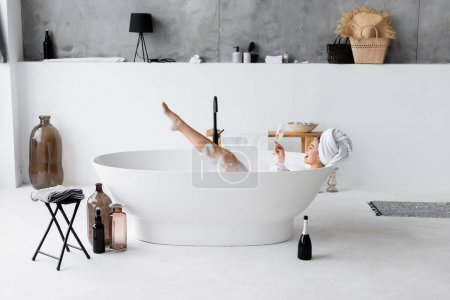 Cheerful woman holding glass of champagne in bathtub