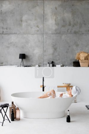 Photo for Young woman drinking champagne while taking bath with foam - Royalty Free Image