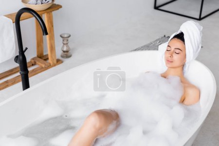 Woman relaxing with closed eyes in modern bathtub