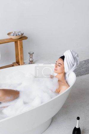 Femme prenant un bain avec mousse près de la bouteille de champagne