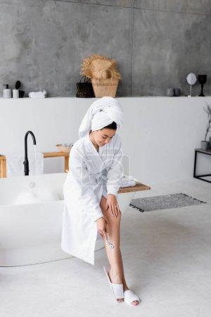 Young woman shaving leg near bathtub at home