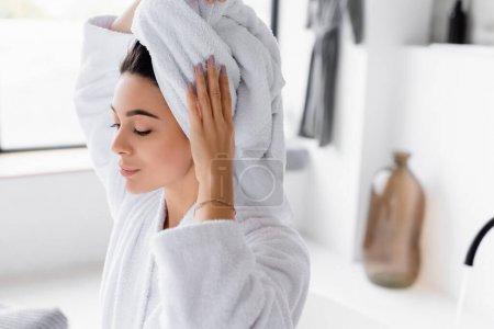 Young woman in bathrobe holding towel on head
