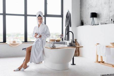 Woman in towel and bathrobe holding cosmetic cream in modern bathroom
