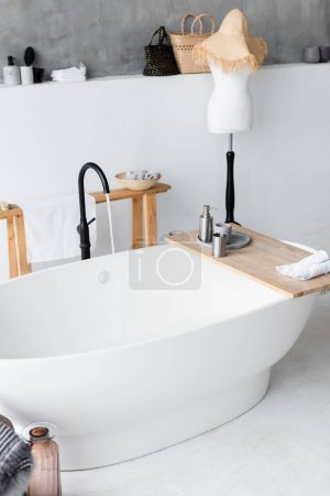 Toiletries on wooden tray on bathtub at home
