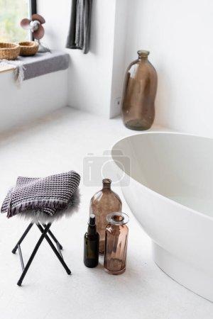 Photo for Decorative bottles near white bathtub at home - Royalty Free Image