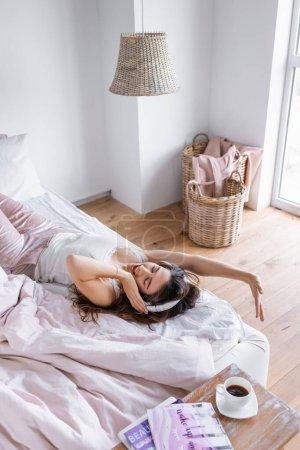 Photo pour Femme gaie dans des écouteurs couchés sur le lit près du café et des magazines au premier plan flou - image libre de droit