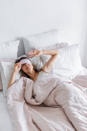 Photo for Brunette woman holding blindfold on bed at home - Royalty Free Image