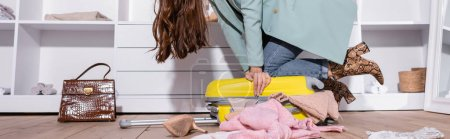 Photo for Cropped view of woman closing suitcase near clothes on floor, banner - Royalty Free Image