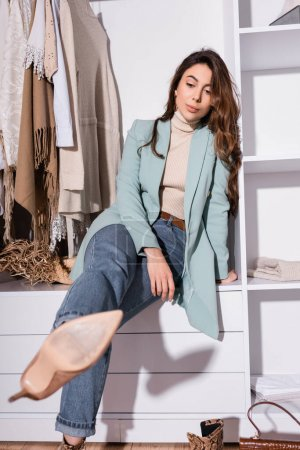 Photo for Brunette woman looking at heeled shoe on blurred foreground in wardrobe - Royalty Free Image