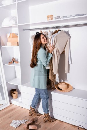 Photo for Smiling woman holding clothes near shoes in wardrobe - Royalty Free Image