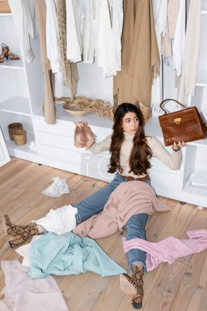 Photo for Brunette woman with shoes and handbag sitting near clothes on floor in wardrobe - Royalty Free Image