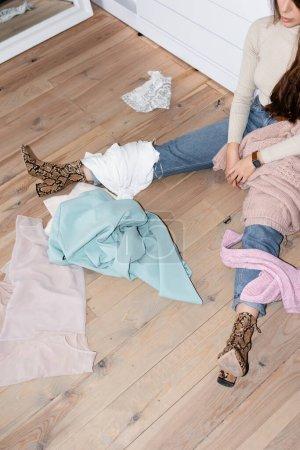 Photo pour Vue recadrée des vêtements sur le sol près de la femme assise dans la garde-robe - image libre de droit