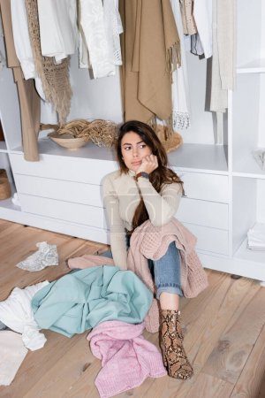 Photo for Thoughtful woman sitting near clothes on floor in wardrobe - Royalty Free Image