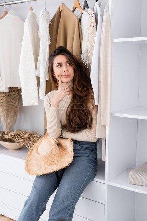 Pensive woman with sun hat sitting on shelf in wardrobe