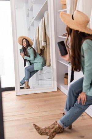 Smiling woman in sun hat holding smartphone near mirror in wardrobe